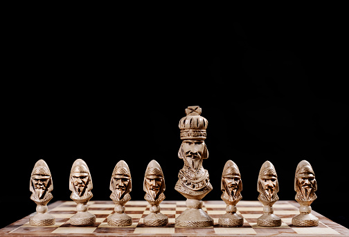 king with pawns on a chessboard on a black background