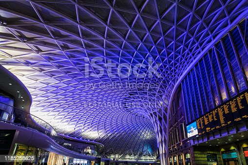 Commuters walking under the modern ceiling inside the departure concourse of King's Cross Station in central London.