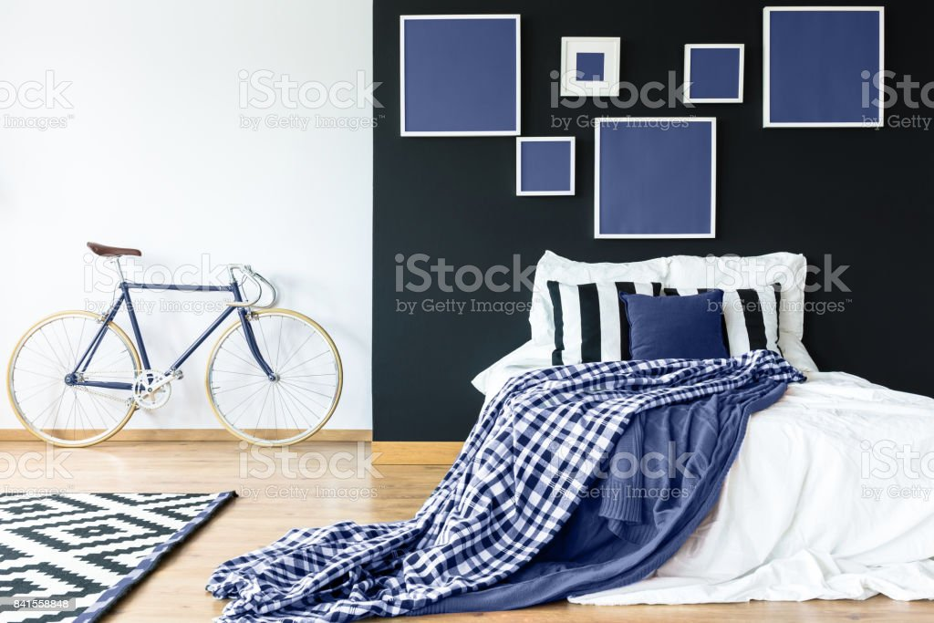 King-size bed against black wall stock photo