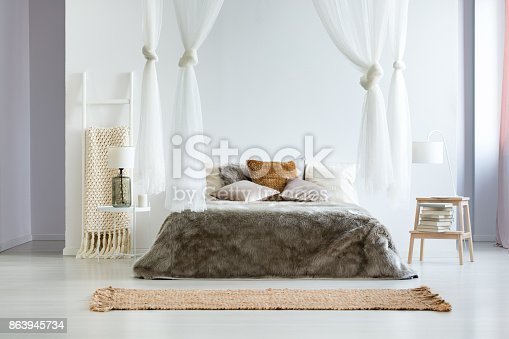 istock King-size bed with fur coverlet 863945734
