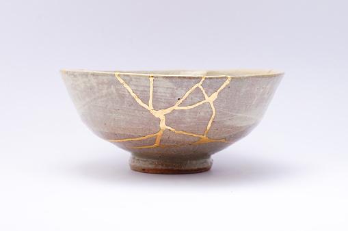 Kintsugi beige bowl. Gold cracks restoration on old Japanese pottery restored with the antique Kintsugi restoration technique. The beauty of imperfections. japanese pottery repair gold. japanese art of repairing cracks with gold. japanese art of fixing broken pottery