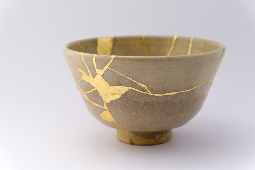 Gold cracks restoration on old Japanese pottery restored with the antique Kintsugi restoration technique. The beauty of imperfections.