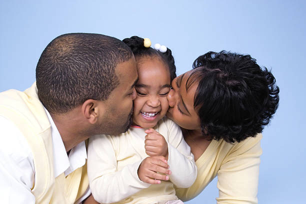 Kiss Attack Parents giving their daughter a kiss attack. little girl kissing dad on cheek stock pictures, royalty-free photos & images