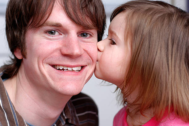 Kiss for Daddy Three-year-old girl giving her daddy a kiss on the cheek. little girl kissing dad on cheek stock pictures, royalty-free photos & images