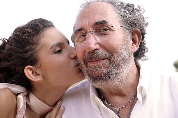bacio sulla guancia. - brunette woman eyeglasses kiss man foto e immagini stock