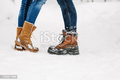 Close up of man and woman legs in boots standing on snow in kiss position