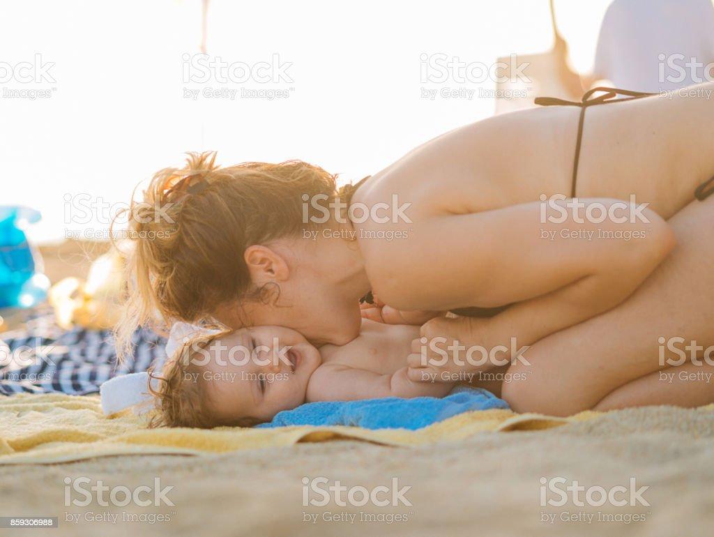 Küssen und umarmen niedliche Baby am Strand Lizenzfreies stock-foto
