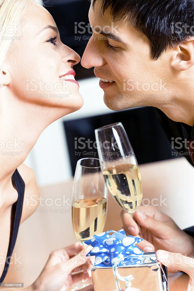 Kissing couple on romantic date or celebrating together at restaurant royalty-free stock photo