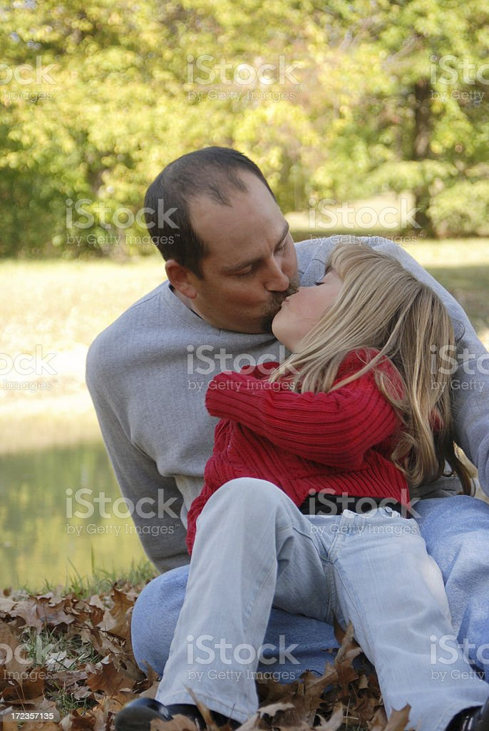 Kissing Daddy in the Leaves stock photo