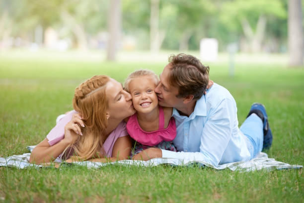 Kissing daughter Father and mother kissing their daughter on both cheeks little girl kissing dad on cheek stock pictures, royalty-free photos & images