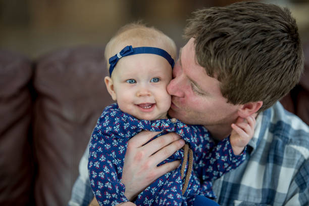 Kissing Daughter A Caucasian father and baby girl are sitting on the couch in their living room. The father is kissing his daughter on the cheek, and she is giggling. little girl kissing dad on cheek stock pictures, royalty-free photos & images