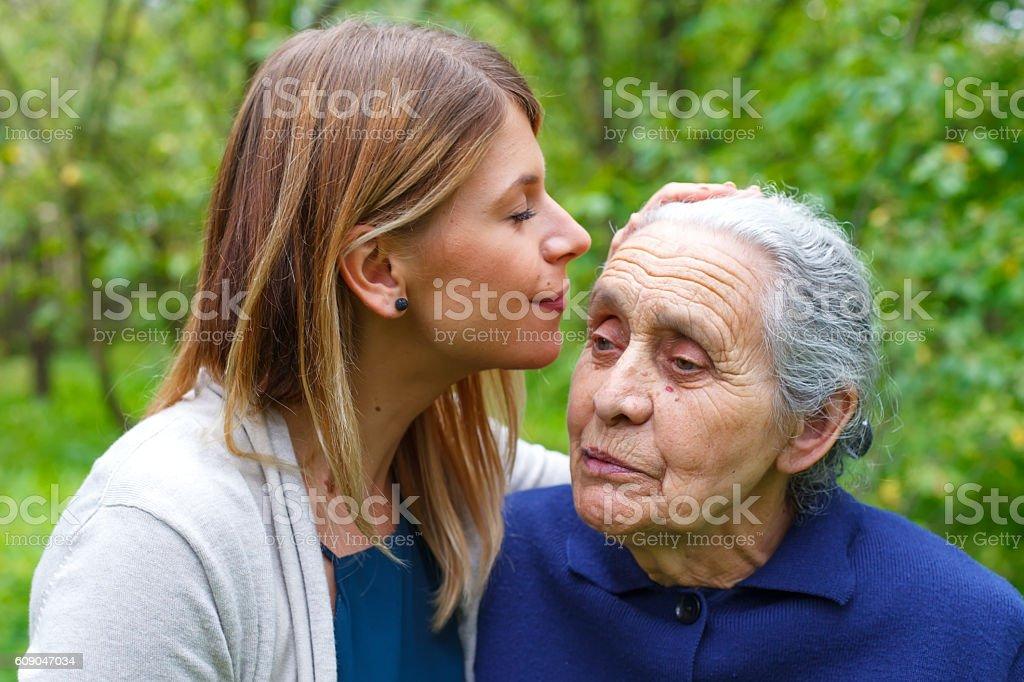 Kissing grandma's forehead - foto de stock