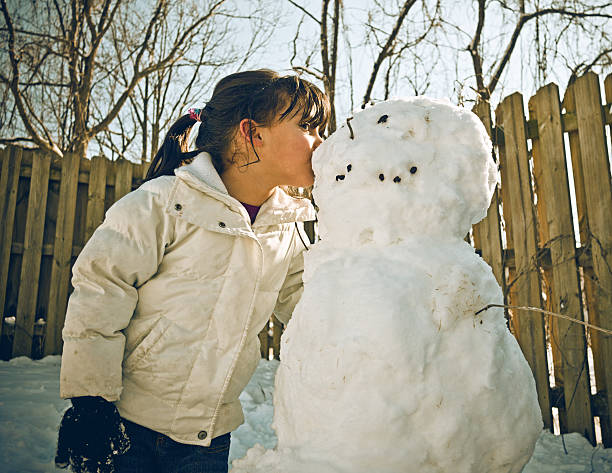 kissing her snowman stock photo