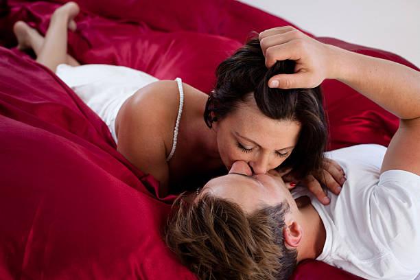 Kissing 異性の若いカップルはベッドで朝のしわ加工 ストックフォト