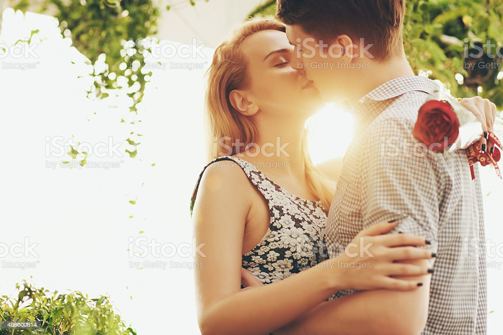 Young couple hugging and kissing at sunset