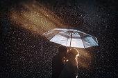 A couple kisses in the rain under an umbrella