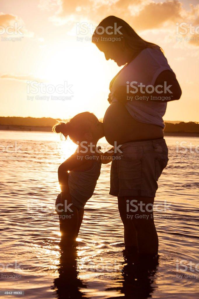 Kissing mum's pregnant tummy stock photo