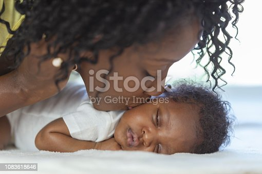 A black mother is kissing her baby boy's cheek as he lies down on a bed.
