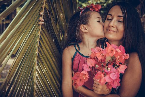 Outdoor Portrait Of Loving Mother  kisses her daughter