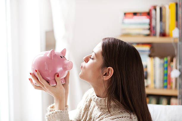 Kissing piggy bank Woman kissing piggy bank miserly stock pictures, royalty-free photos & images