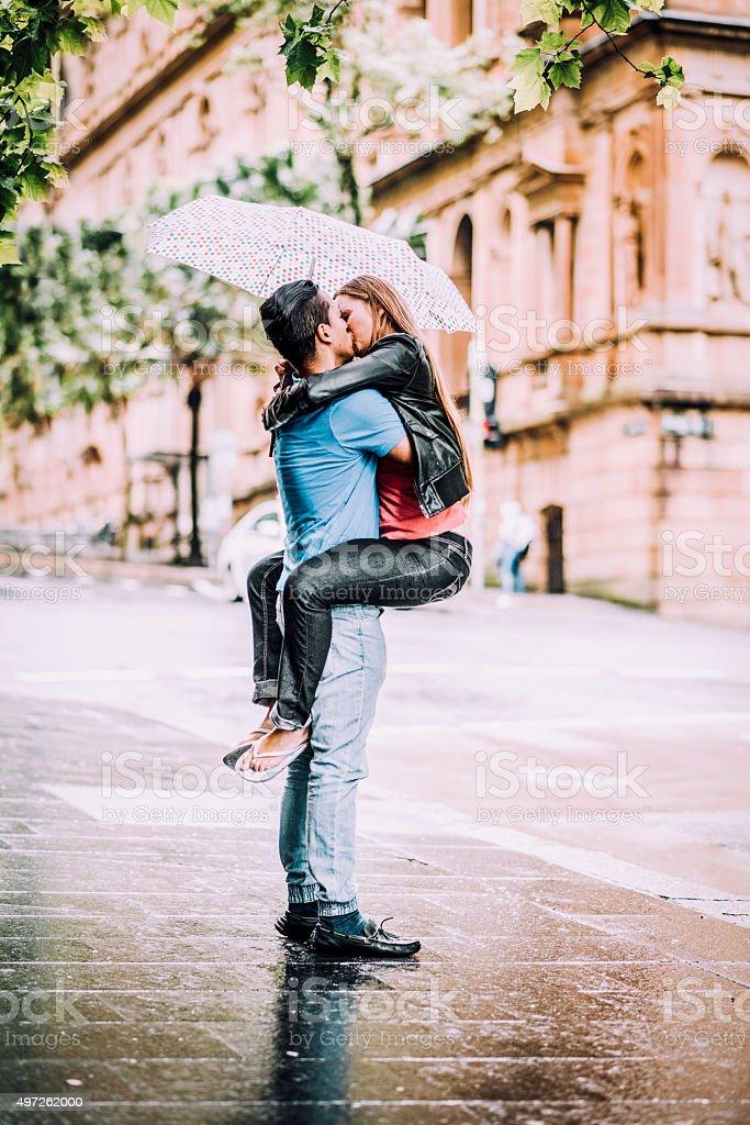 Kissing under Umbrella stock photo