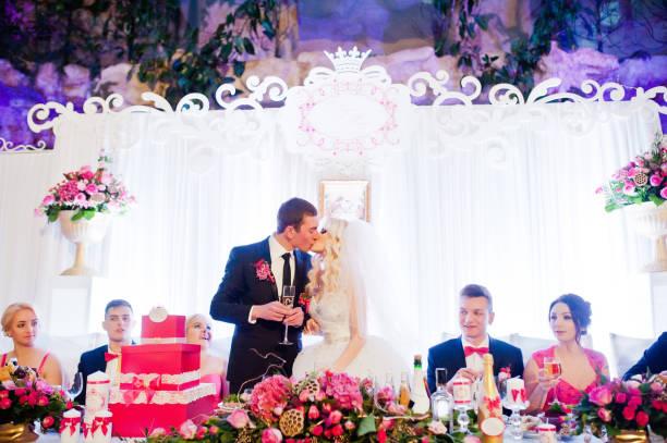 küssende brautpaar an der hochzeitstafel im restaurant - bräutigam tisch stock-fotos und bilder