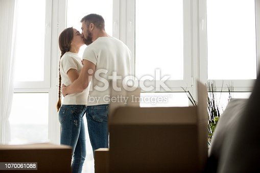 938682826istockphoto Kissing young couple in new apartment with unpacked belongings 1070061088
