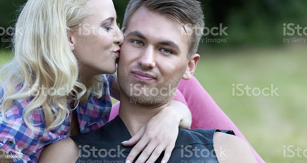 kissing young couple in park royalty-free stock photo