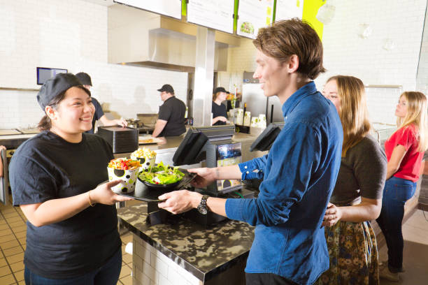 Kitchen and Wait Staff Serving Customers in Fast Food Restaurant stock photo