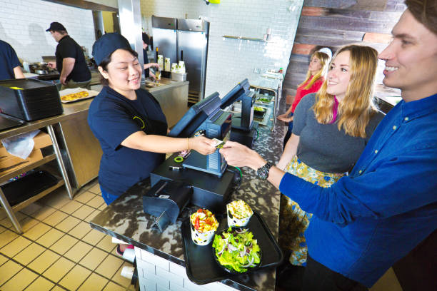 kitchen and wait staff serving customers in fast food restaurant checkout - fast food restaurant stock pictures, royalty-free photos & images