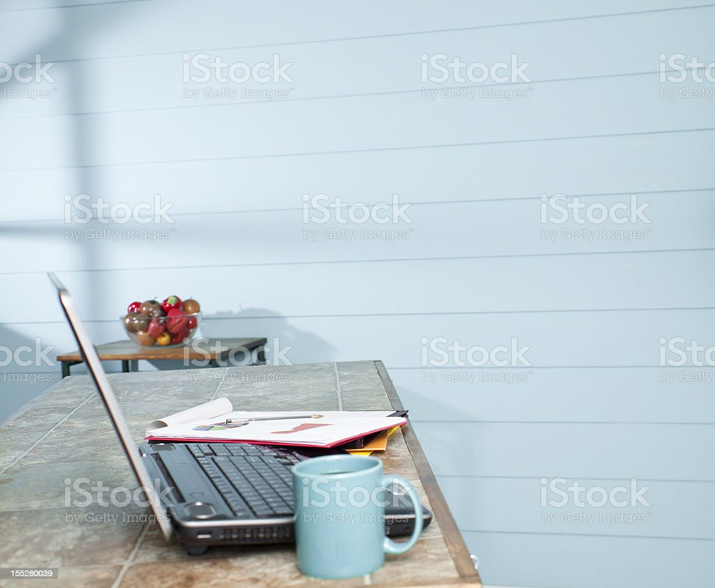 Kitchen bar with laptop, paperwork, coffee. Working from home. Telecommuting. royalty-free stock photo