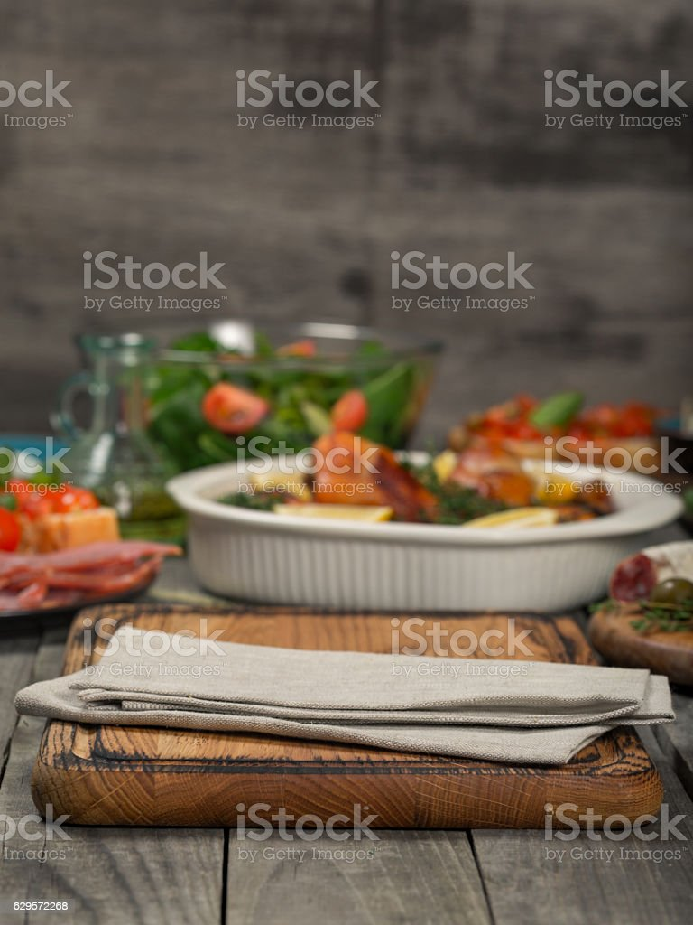 kitchen board with a cloth on wooden table in the background baked...