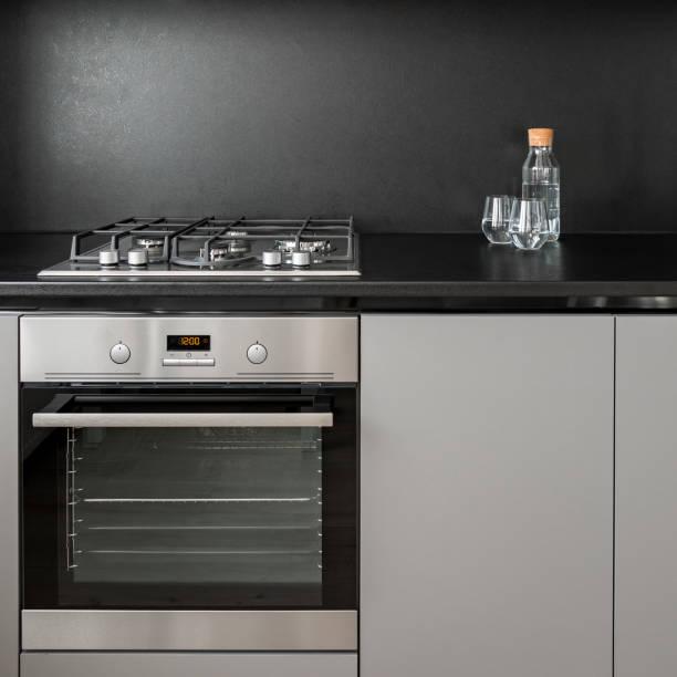 armoires de cuisine et dosseret noir - cuisinière photos et images de collection