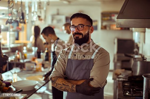 Close up of a kitchen chef taking a photo while working in a kitchen with his coworkers