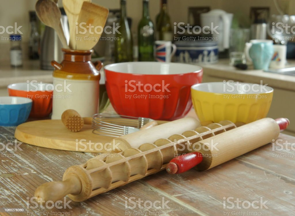 A kitchen counter with utensils, rolling pins, cutting boards, bowls, and more stock photo