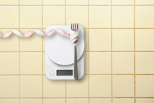 Kitchen digital food weight scale with measuring tape on kitchen tile. stock photo