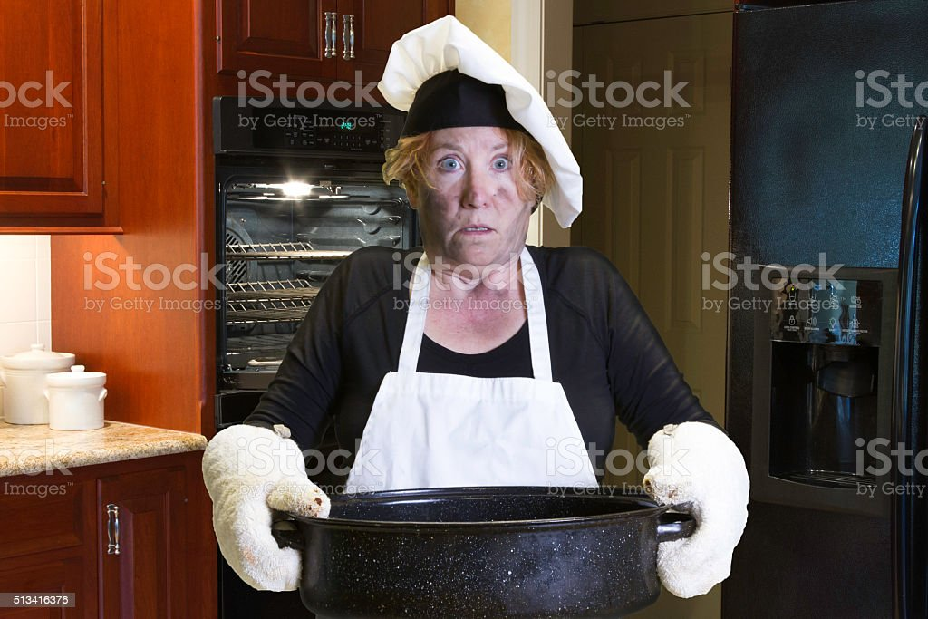 Kitchen disaster with apron and chef hat stock photo