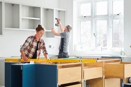 a female kitchen fitting cupboards for worktop