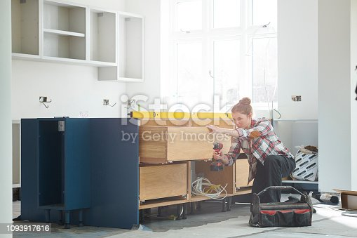 a female kitchen fitter prepping cupboards for worktop