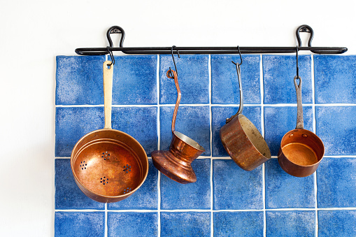 Kitchen interior, accessories. Hanging copper kitchenware set