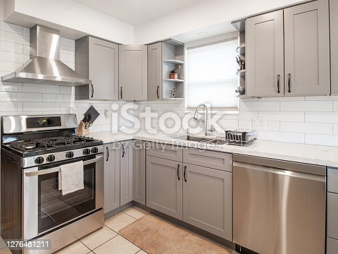 a small modern kitchen with grey cabinets and stainless steel appliances and a decorative bowl .