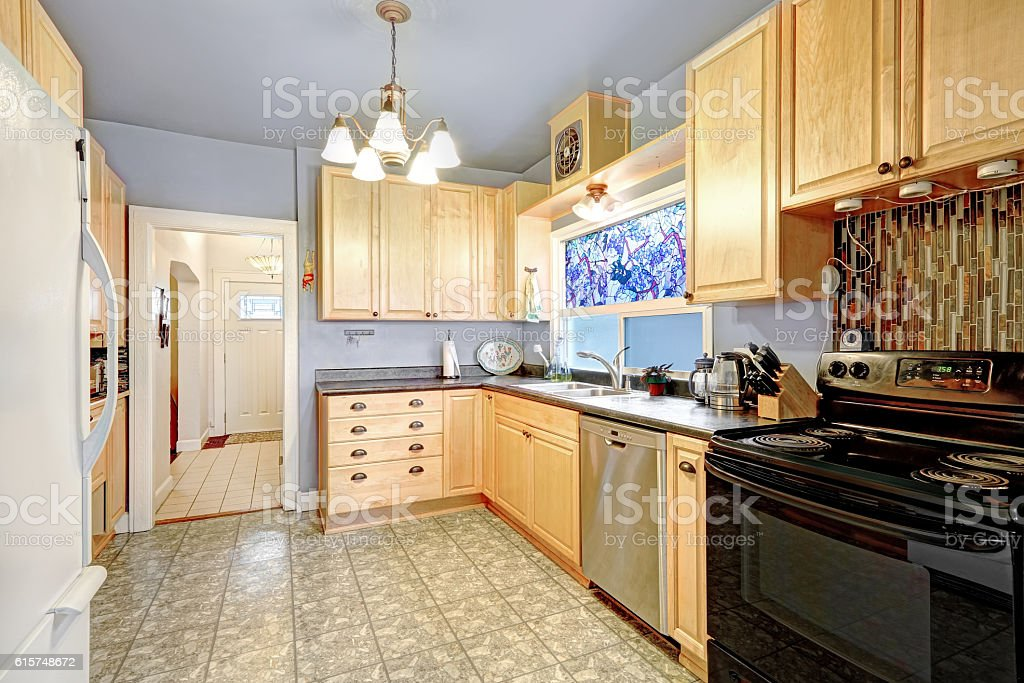Kitchen Interior With Golden Cabinets, Black And White Appliances  Royalty Free Stock Photo