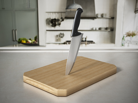 Kitchen knife on cutting wood standing on kitchen counter.