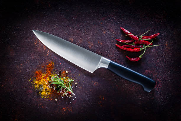 Kitchen knife shot on dark background Stainless steel kitchen knife with a black handle shot from above on dark abstract background. A group of dried red chili peppers are at the top-right of the knife and a powdered spices and a rosemary twig are at the bottom-left of an horizontal frame. Low key DSRL studio photo taken with Canon EOS 5D Mk II and Canon EF 100mm f/2.8L Macro IS USM kitchen knife stock pictures, royalty-free photos & images