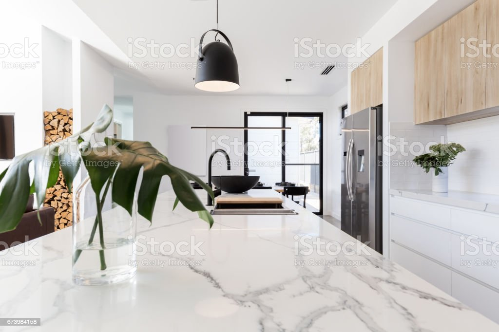 Kitchen marble bench close up with black hanging pendant stock photo