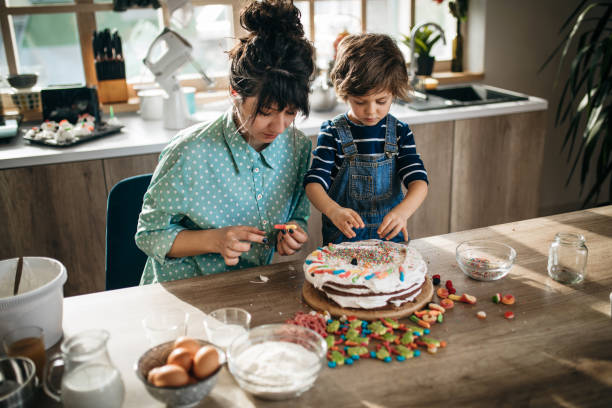 Kitchen miracles Single mom and her son decorating a cake in the kitchen decorating a cake stock pictures, royalty-free photos & images