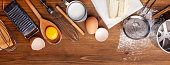 istock Kitchen, pastry inventory lies on the wooden table. Butter, eggs, wooden spoons, whisk, flour, milk. Top view with copy space, mockup for menu, recipe for culinary classes. Baking background Image. Banner 1084962490