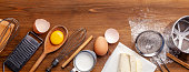 istock Kitchen, pastry inventory lies on the wooden table. Butter, eggs, wooden spoons, whisk, flour, milk. Top view with copy space, mockup for menu, recipe for culinary classes. Baking background Image. Banner 1084962504