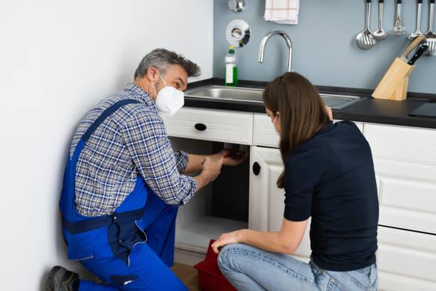 Kitchen Pipe Damage Problem. Woman And Repairman stock photo