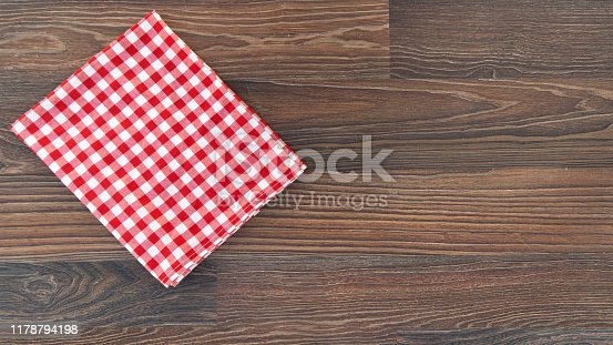 937183584 istock photo Kitchen plaid textile on old rustic wood. Food menu background Red checkered tablecloth 1178794198